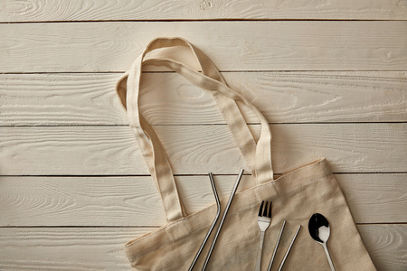 top view of cutlery items and cotton bag on white wooden surface, zero waste concept
