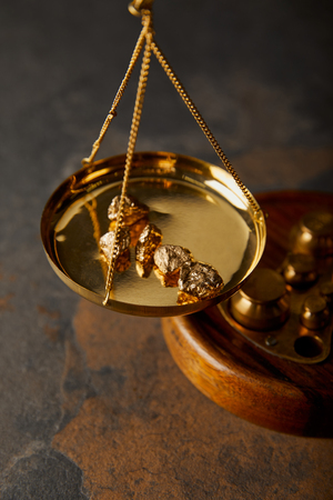 golden stones on scales on marble table Фото со стока