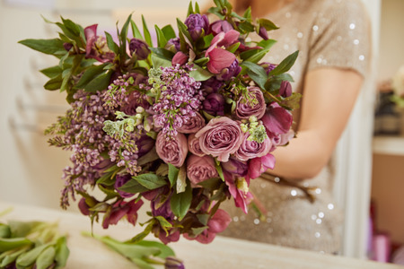 partial view of florist making bouquet of purple tulips, peonies and lilac