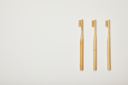 top view of bamboo brown toothbrushes on white background