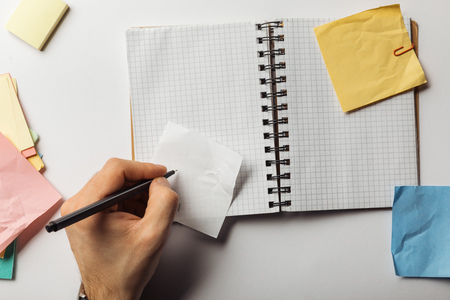 cropped view of man writing on sticky note near opened notebook