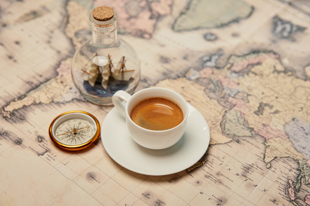 selective focus of coffee cup, compass and toy ship in glass bottle on map Banque d'images - 118536650