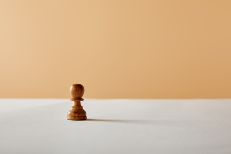 wooden pawn piece on white table and beige background