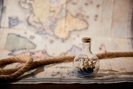 rope, toy ship in glass bottle and map on wooden table Foto de archivo - 118536253