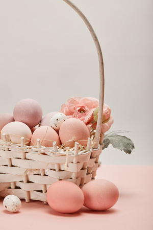 close up of easter chicken and quail eggs in straw basket with flower