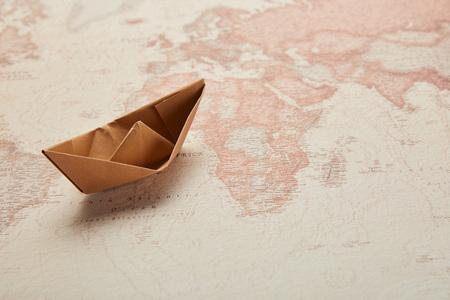 paper boat on vintage world map