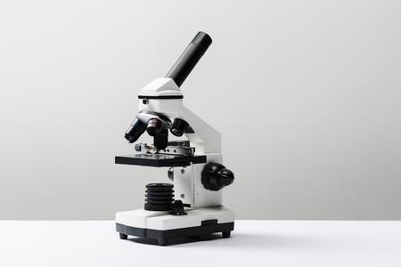 microscopio sobre fondo gris con espacio de copia