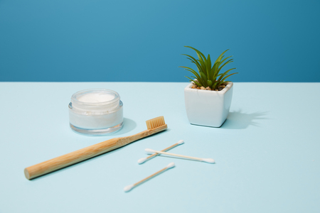 bamboo toothbrush, cosmetic cream and plant in pot on table and blue background
