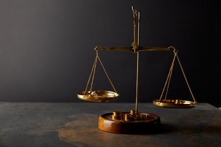 goldene Steine auf Skalen auf Marmortisch und dunklem Hintergrund Standard-Bild