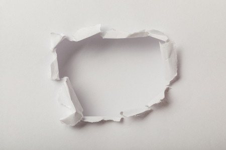 torn hole in sheet of paper on white background
