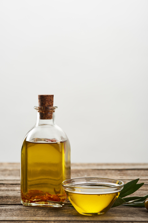bottle and glass bowl of olive oil, olive tree leaves and olives on wooden surface