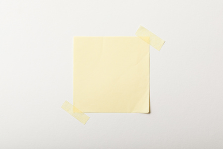 yellow blank paper with sticky tape on white background