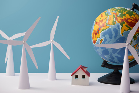 windmill and house models with globe on white table and blue background