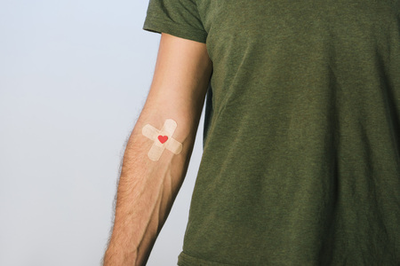 Partial view of patient in green t-shirt with plasters on grey background, blood donation concept