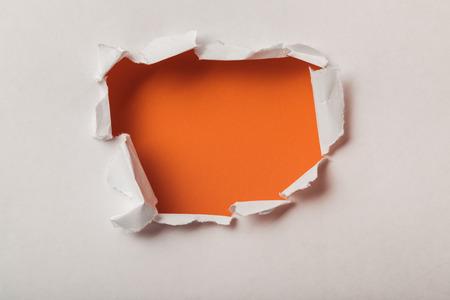 zerrissenes Loch im Blatt Papier auf orangem Hintergrund Standard-Bild