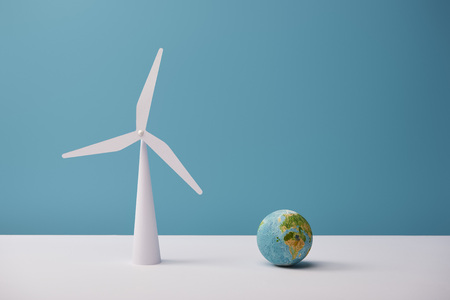small globe and windmill model on white table and blue background