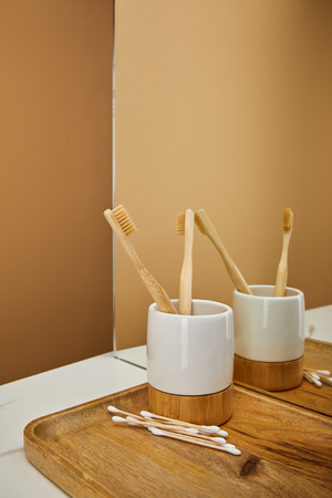 board with bamboo toothbrushes in holder and ear sticks beside mirror on white table and beige background