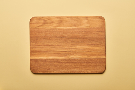 top view of empty wooden chopping board on yellow background 免版税图像
