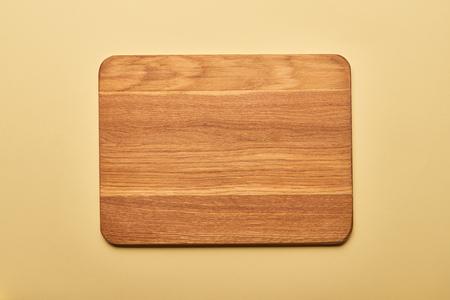 Vista superior de la tabla de cortar de madera vacía sobre fondo amarillo