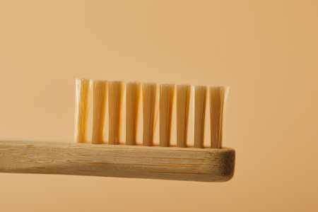 close up view of brown bamboo toothbrush on beige background Stock Photo