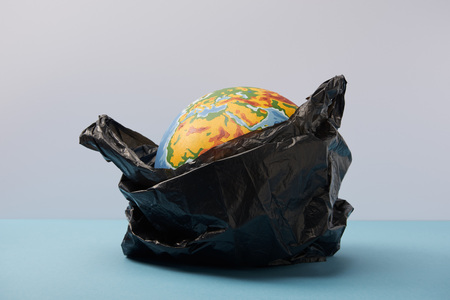 globe in black polyethylene bag on blue table and background Banco de Imagens