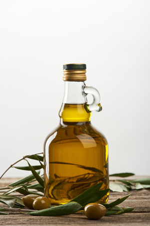 bottle of oil with olive tree leaves and olives isolated on grey 스톡 콘텐츠