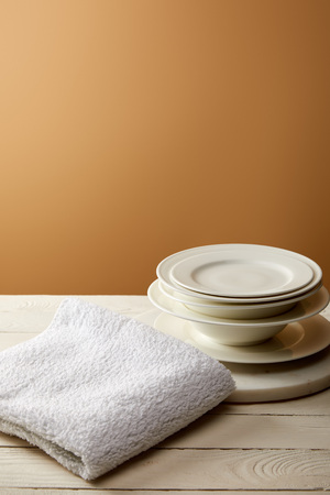 stack of plates and terry cotton towel on white wooden surface Stock Photo