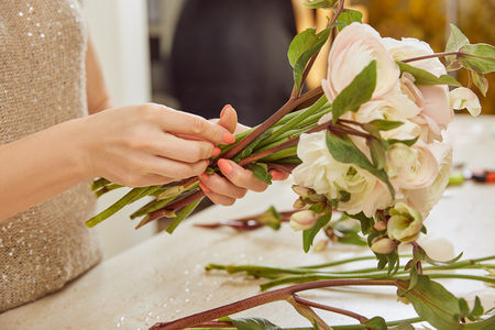 cropped view of florist making bouquet of white peonies at workspace