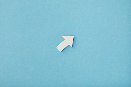 top view of white diagonal arrow on blue background
