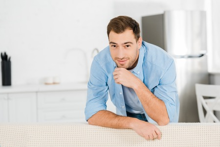 handsome smiling man propping chin with hand, leaning on sofa and looking at camera at home Stok Fotoğraf