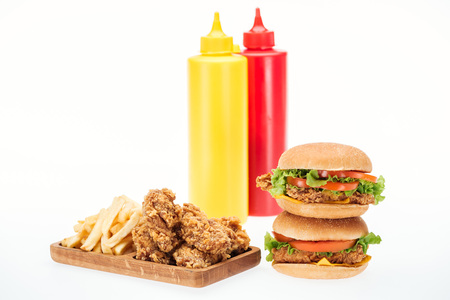 crispy chicken nuggets, hamburgers and french fries near bottles with ketchup and mustard isolated on white