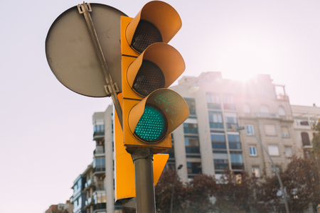 selective focus of traffic light with multistory house on background, barcelona, spain