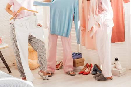 cropped view of girls choosing clothes in wardrobe Stock Photo