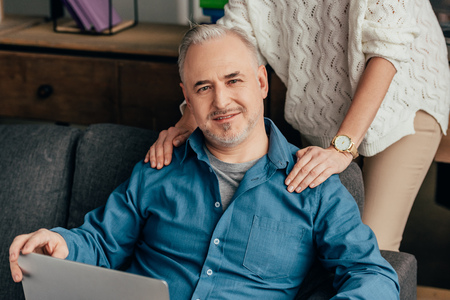 cropped view of woman standing near cheerful husband with laptop Stock Photo