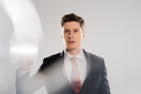 selective focus of young businessman gesturing on grey