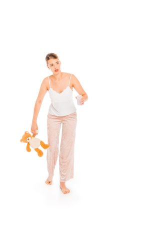 girl in pyjamas holding teddy bear and glass isolated on white Stock fotó