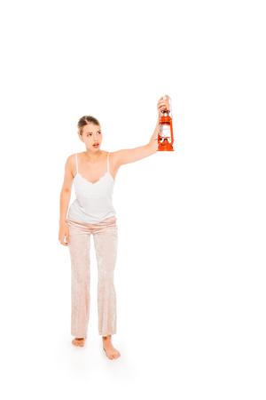 floating girl in pyjamas holding lantern isolated on white