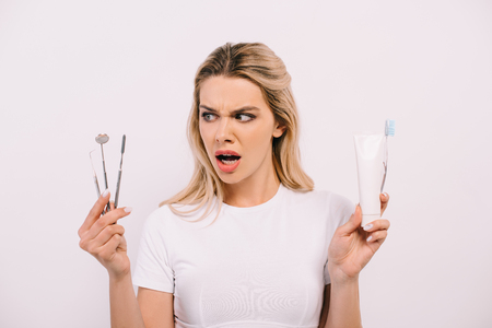 beautiful shocked woman holding toothpaste, toothbrush and dental instruments isolated on white