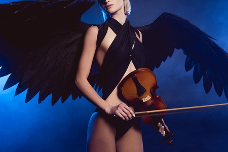 cropped view of woman with black angel wings and violin on dark blue background