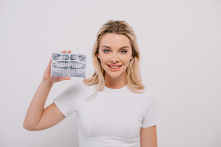 beautiful woman in t-shirt holding teeth x-ray isolated on white Imagens