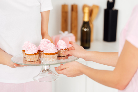 cropped view of girl taking pink cupcake from glass stand