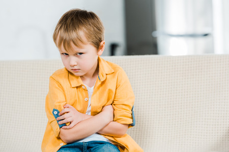 dissatisfied preschooler boy sitting with arms crossed and looking at camera at home
