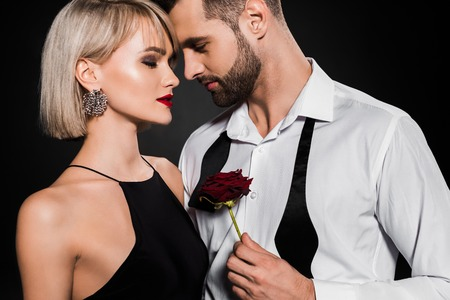 handsome bearded man holding red rose and embracing passionate girl, isolated on black Banco de Imagens