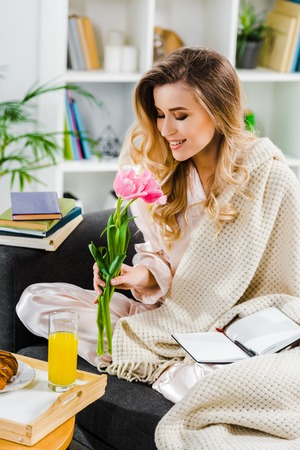 Romantic girl with knitted plaid sniffing pink flowers at home Banco de Imagens