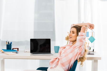 Relaxed young woman in checkered shirt sitting with closed eyes at workplace