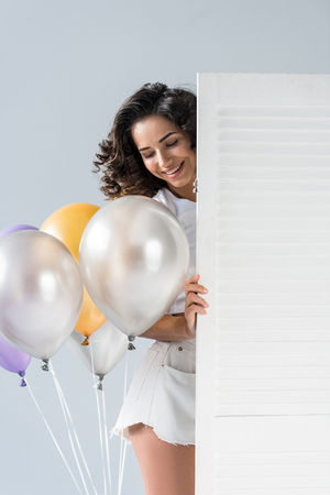 Blissful curly young woman with air balloons on grey background