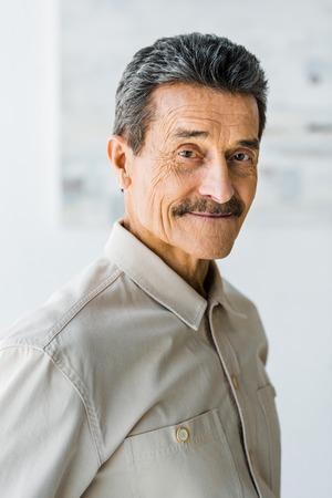 alegre, hombre mayor, con, bigote, mirar cámara del juez, y, sonriente, en casa Foto de archivo