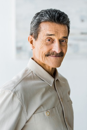 cheerful senior man with mustache looking at camera and smiling at home Archivio Fotografico