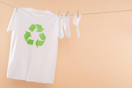 T-Shirt mit Recycling-Schild auf der Wäscheleine in der Nähe von weißen Socken isoliert auf Beige, umweltfreundliches Konzept Standard-Bild