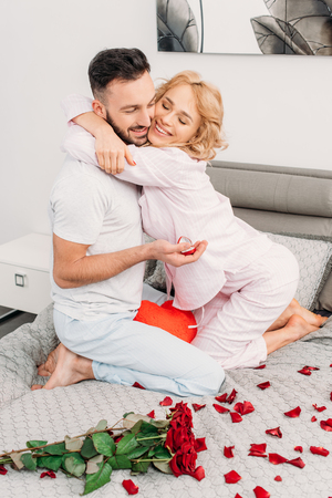 Man with ring box embracing with girlfriend on bed Stock Photo